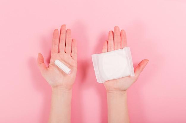Weibliche hände halten eine damenbinde und einen tampon auf einem rosa.