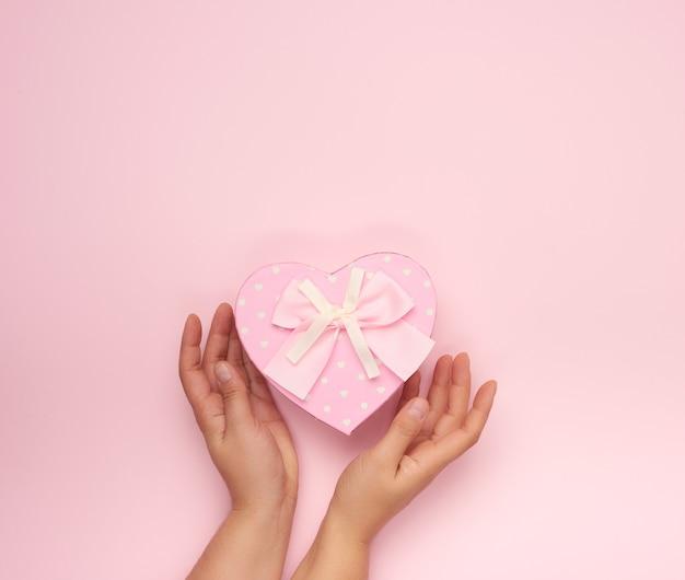Weibliche hände halten eine geschlossene rosa schachtel aus papier in form eines herzens