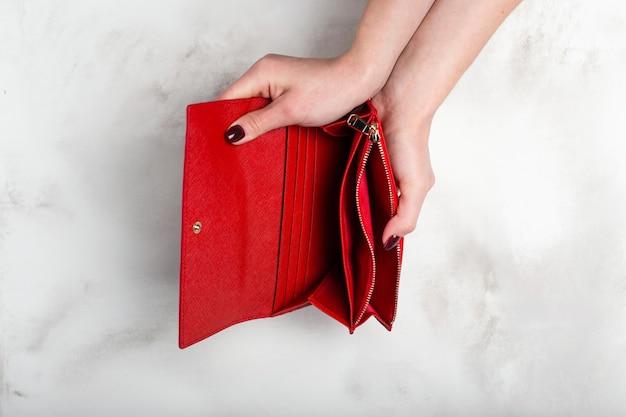 Weibliche hände halten eine leere stilvolle rote geldbörse auf weißer granitbeschaffenheit