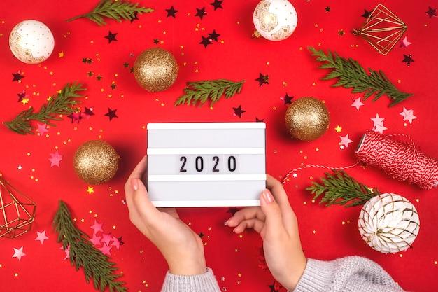 Weibliche hände halten eine rechteckige verzierung mit aufschrift 2020. neues jahr-konzept.