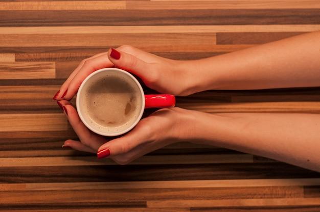 Weibliche hände halten eine tasse kaffee mit schaum über holztisch, draufsicht. weibliche hände halten tasse kaffee auf holzuntergrund