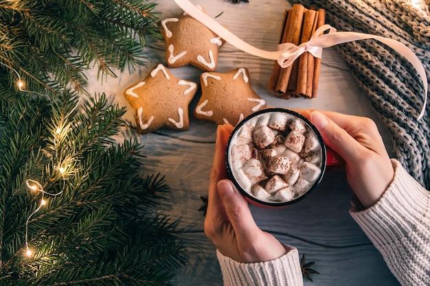 Weibliche hände halten eine tasse kaffee oder tee auf einem marshmallow. weihnachts- oder neujahrskomposition aus heißem getränk, ingwerplätzchen und zimt. draufsicht.