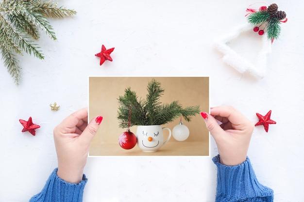 Weibliche hände halten eine weihnachtsgrußkarte auf dem hintergrund eines weißen tisches mit weihnachtsdekor.