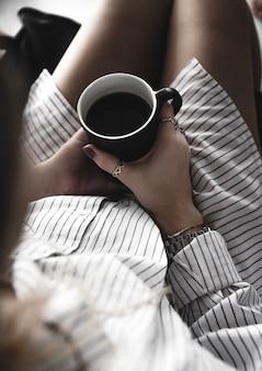 Weibliche hände halten eine weiße tasse tee, burgunder maniküre, das mädchen ist in ein hemd gekleidet