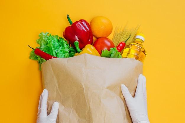 Weibliche hände halten einen roten, gelben pfeffer, chili, sonnenblumenöl, tomate, orange, nudeln, salat in papierhandwerkspaket, ein satz veganes essen auf einem orangefarbenen raum