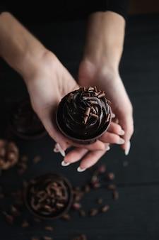 Weibliche hände halten einen schokoladenmuffin oder einen cupcake auf einem dunklen hintergrund. mehrere muffins oder cupcakes mit schokoladenförmiger sahne am schwarzen tisch. festliche kerze brennt auf einem schokoladenkuchen.