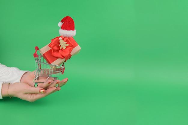 Weibliche hände halten einkaufswagen des einkaufswagens mit geschenk, das weihnachtsmannmütze in auf einem grünen festlichen hintergrund trägt