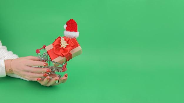 Weibliche hände halten einkaufswagen des einkaufswagens mit geschenkbox, die weihnachtsmannmütze auf grün trägt