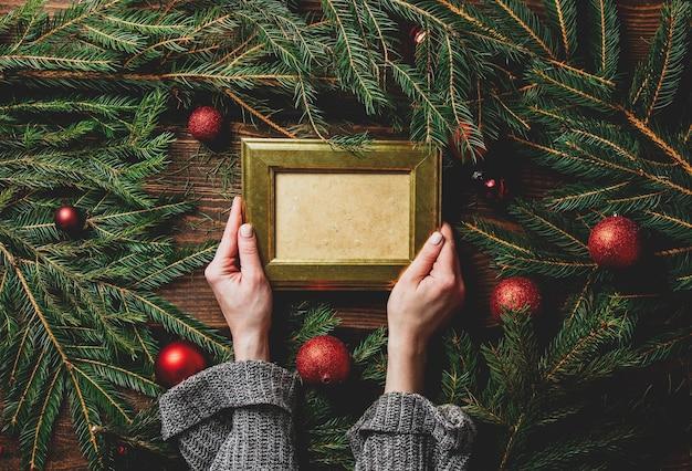 Weibliche hände halten fotorahmen neben weihnachtsdekoration