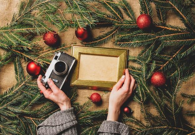 Weibliche hände halten fotorahmen und kamera neben weihnachtsdekoration