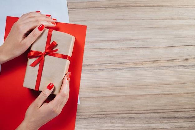 Weibliche hände halten geschenkbox in bastelpapier gewickelt und mit rotem satinband verziert