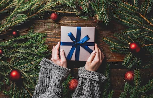 Weibliche hände halten geschenkbox neben weihnachtsdekoration auf einem tisch