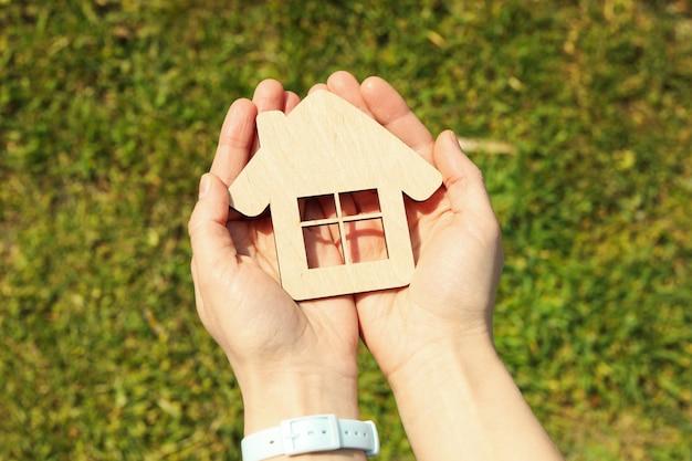 Weibliche hände halten holzhaus. eine immobilie kaufen