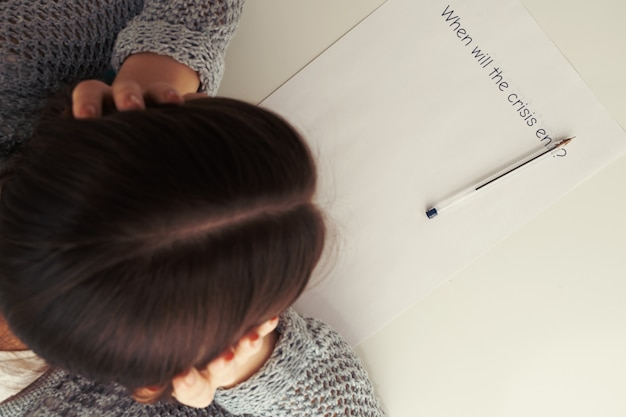 Weibliche hände halten ihren kopf über ein blatt papier mit der inschrift, wenn die krise endet