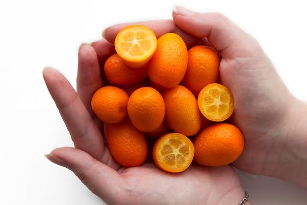 Weibliche hände halten japanische orangen (mandarinen) in form eines herzens auf einem weißen hintergrund.
