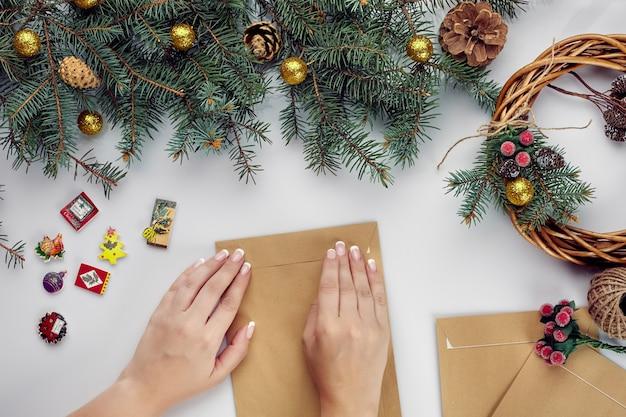 Weibliche hände halten karte der frohen weihnachten und umschlagweihnachtsdekorationshintergrund flach draufsicht