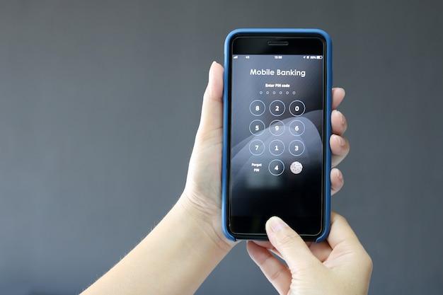 Weibliche hände halten mobile banking am smartphone