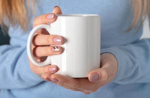Weibliche hände halten nachgebildete weiße leere tasse, tasse für ihr design und logo-nahaufnahme. leere vorlage für werbetextnachrichten oder werbeinhalte.