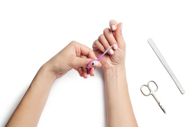 Weibliche hände halten nagelscheren, neben geräten für die nagelpflege. das mädchen macht eine maniküre. isoliert auf weißem hintergrund. von oben betrachten. hochwertiges foto