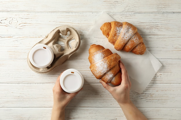 Weibliche hände halten pappbecher kaffee und croissant auf hölzernem hintergrund, draufsicht
