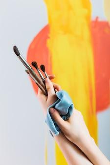 Weibliche hände halten pinsel, die ein bild auf einer staffelei malen