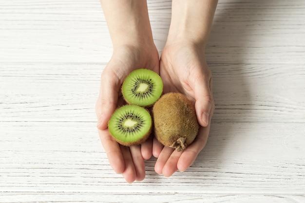 Weibliche hände halten reife kiwi