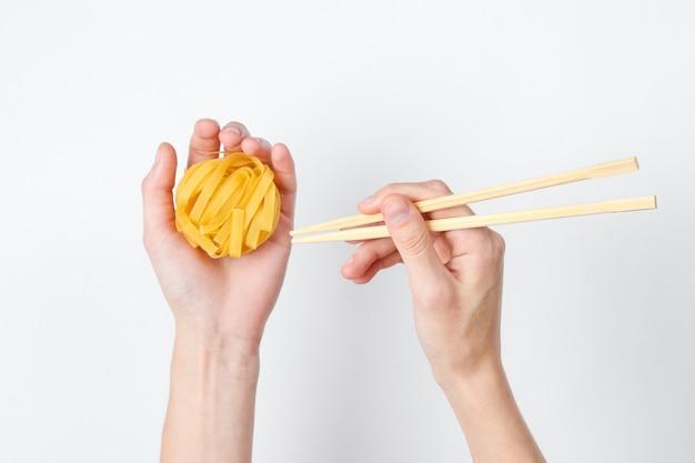 Weibliche hände halten rohe tagliatelle-nudeln und essstäbchen auf weiß. minimalistisches lebensmittelkonzept. draufsicht