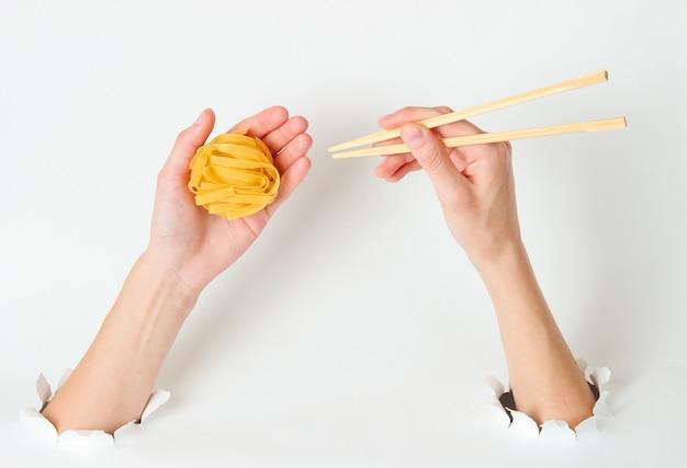 Weibliche hände halten rohe tagliatelle-nudeln und essstäbchen auf weiß mit zerrissenem loch. minimalistisches lebensmittelkonzept. draufsicht
