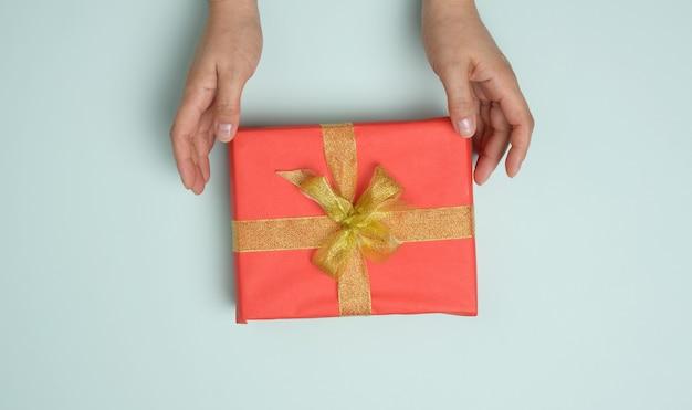 Weibliche hände halten rote geschenkbox auf blauem hintergrund, konzept der glückwünsche