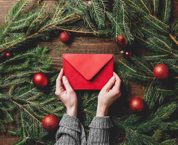 Weibliche hände halten rote post neben weihnachtsdekoration