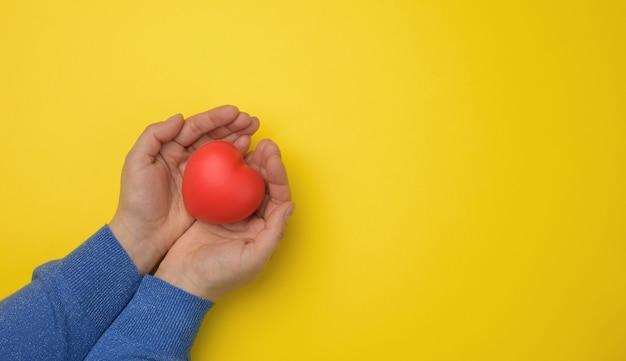 Weibliche hände halten rotes textilherz, blauen hintergrund. liebes- und spendenkonzept, kopierraum
