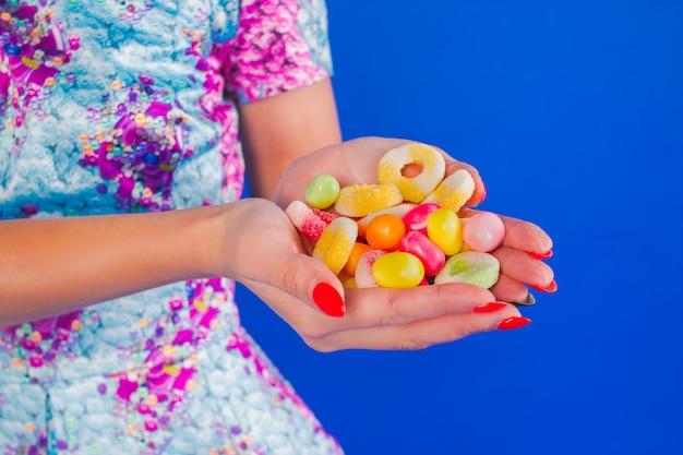 Weibliche hände halten süße süßigkeiten lokalisiert auf blauem hintergrund. schließen sie die auswahl der verschiedenen bunten süßigkeiten im bäckereigeschäft .candy store ab. party-snack-food-konzept. ungesundes essen für kinderzähne.