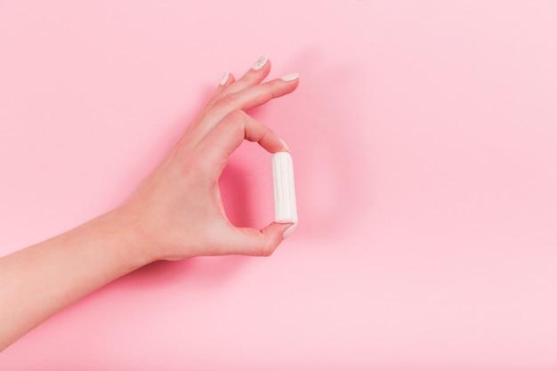 Weibliche hände halten tampon auf einem rosa.