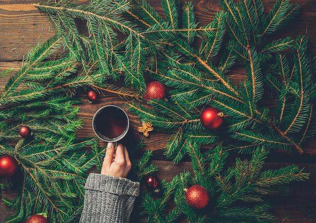 Weibliche hände halten tasse tee mit weihnachtsbaum auf einem tisch