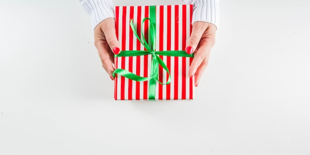 Weibliche hände halten weihnachtsgeschenkboxen, -champagner und -gläser
