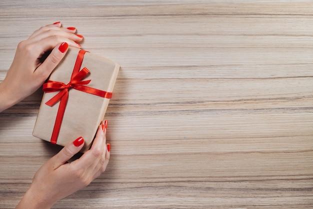 Weibliche hände halten weihnachtsgeschenkboxen verziert mit satinbändern auf hölzernem hintergrund