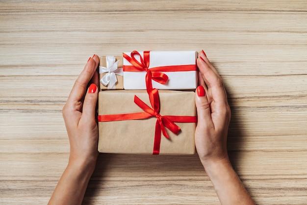 Weibliche hände halten weihnachtsgeschenkboxen verziert mit satinbändern auf holzoberfläche