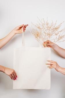 Weibliche hände halten wiederverwendbare ökobeutel-mocku aus baumwolle weißer beutel auf weißem, isoliertem hintergrund mit zweig ...