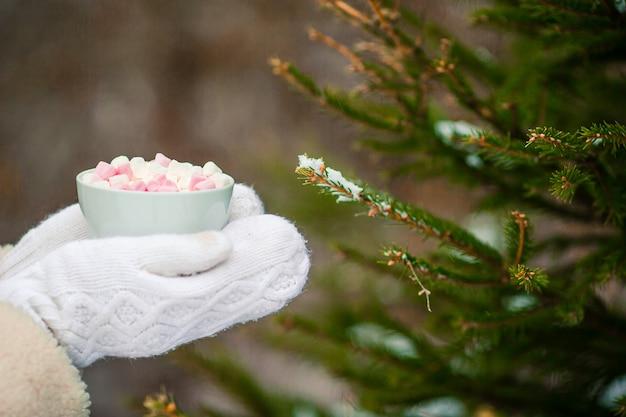 Weibliche hände holdink weißer tasse kaffee mit den weißen und rosa eibischen