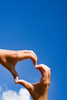 Weibliche hände in der form eines herzens über himmel. liebes- oder gesundheitskonzept