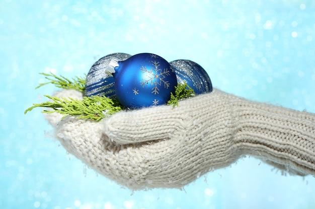 Weibliche hände in fäustlingen weihnachtsbaumkugeln, auf farboberfläche