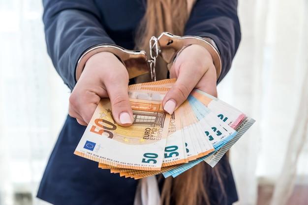 Weibliche hände in fesseln, die euro-banknoten anbieten