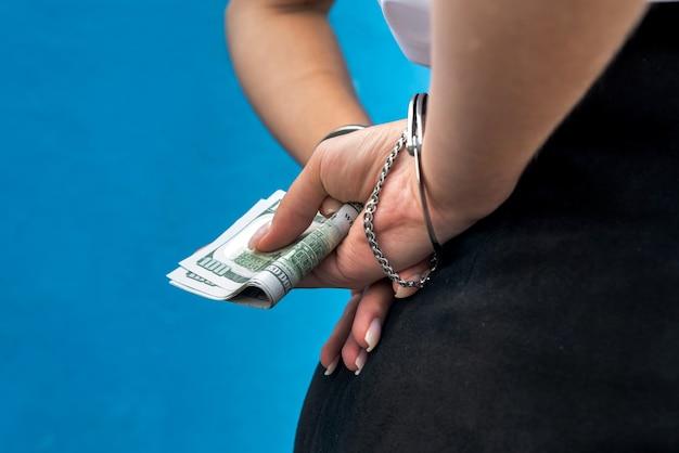 Weibliche hände in handschellen halten dollars isoliert auf blau. gefangener oder verhaftet