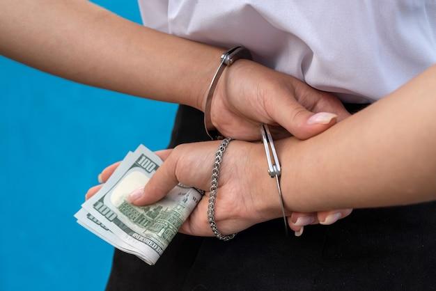 Weibliche hände in handschellen halten uns geld.