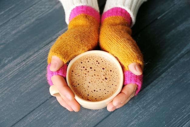 Weibliche hände in handschuhen, die eine tasse kaffee auf holzoberfläche halten