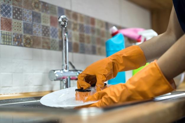 Weibliche hände in handschuhen, die geschirr über dem waschbecken in der küche spülen