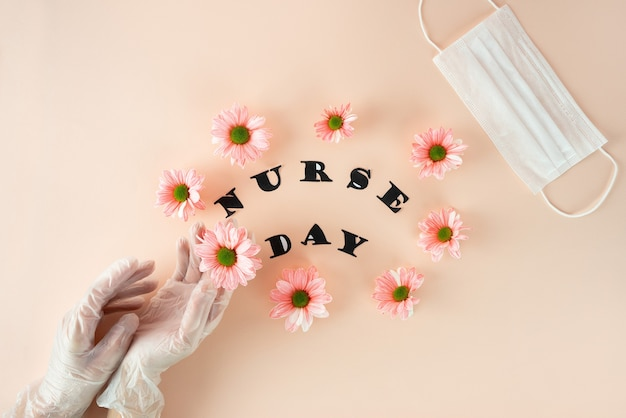 Weibliche hände in handschuhen halten eine rosa chrysantheme auf einem pastellrosa hintergrund mit einem weißen medizinischen