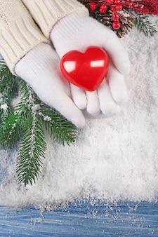 Weibliche hände in handschuhen mit dekorativem herzen auf schnee