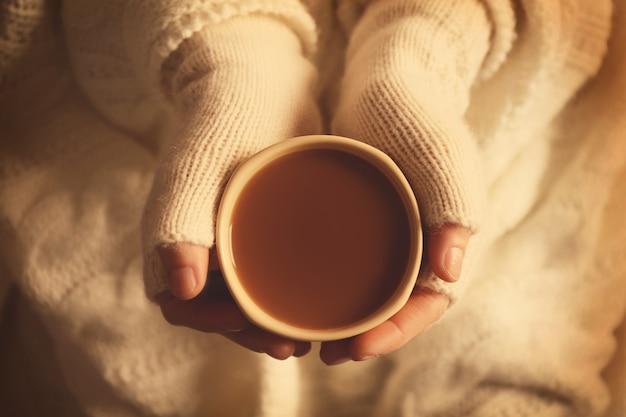 Weibliche hände in handschuhen mit einer tasse kaffee, nahaufnahme