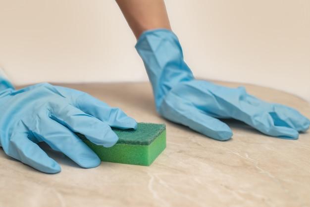Weibliche hände in handschuhen waschen einen schmutzigen tisch mit einem schwamm drinnen